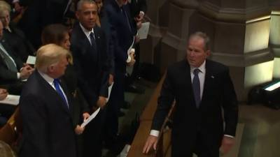 George W. Bush has sweet exchange with Michelle Obama at father's funeral